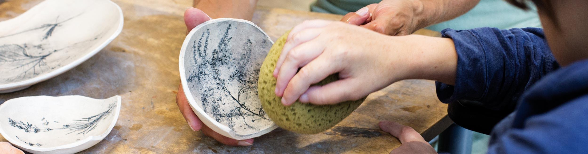 Headerbild: Hand bearbeitet mit Schwamm eine Porzellanschale