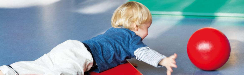 Kind liegt auf dem Bauch und spielt mit einem roten Ball